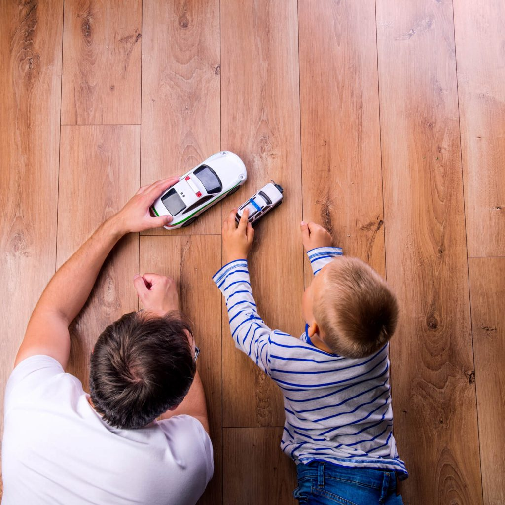 Father with kid playing with toycar | Lake Forest Flooring